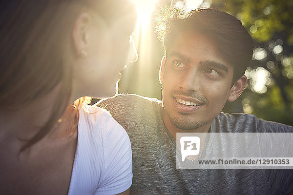 Romantic young couple sitting in park  enjoying sunset