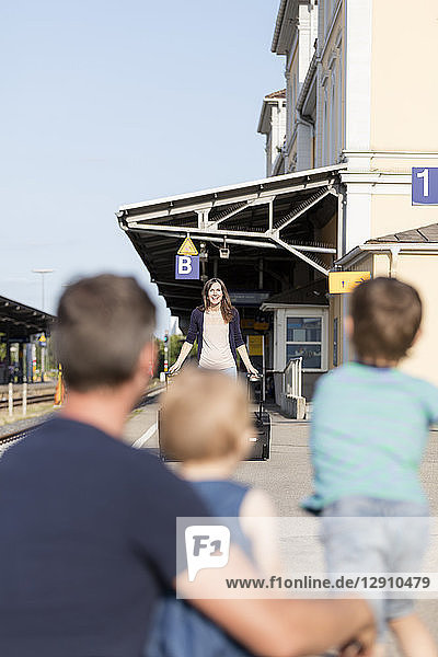 Family welcoming arriving mother on platform