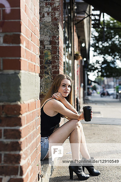 Young woman sitting in the street on a doorstep  holding a cup of coffee