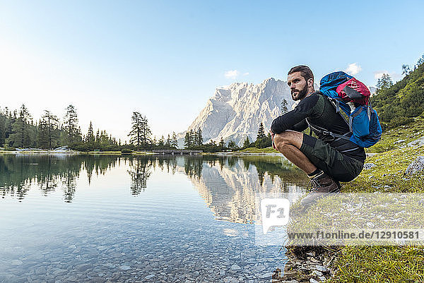 Austria  Tyrol  Hiker taking a break  crouching by the lake