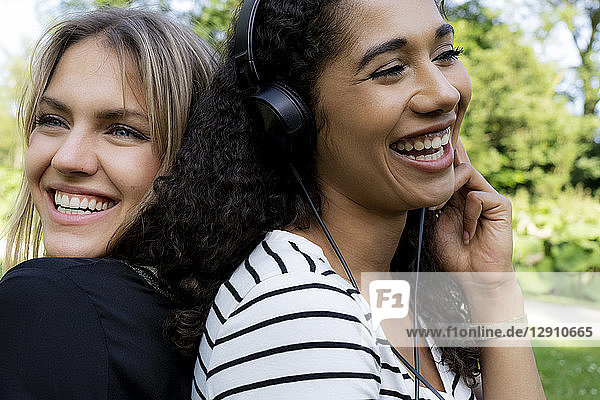 Two girlfriends in a park listening music  laughing  having fun