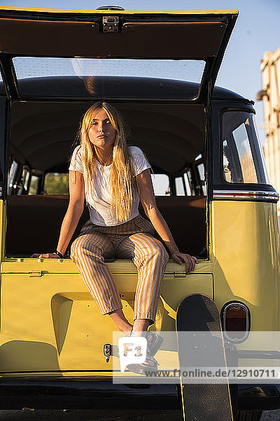 Young woman with skateboard sitting in a vintage van