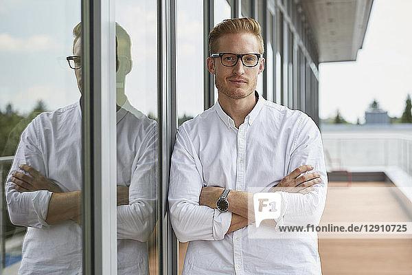 Portrait of confident businessman leaning against window