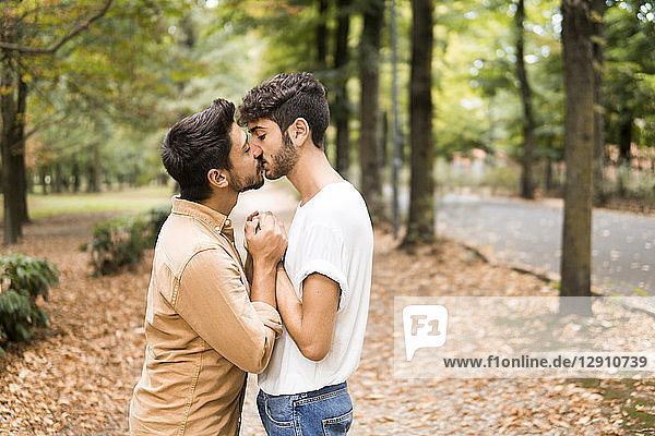 Young gay couple holding hands and kissing in autumnal park