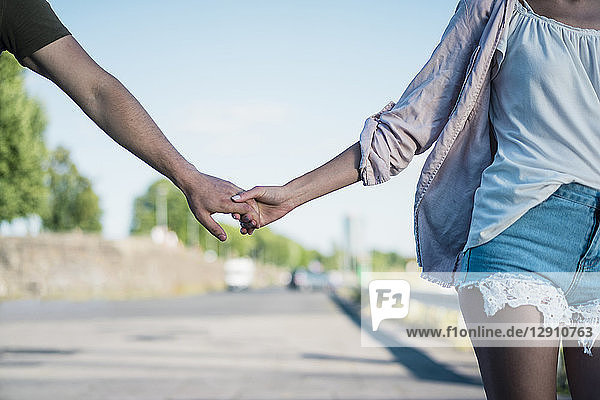 Close-up of couple hand in hand on waterfront promenade