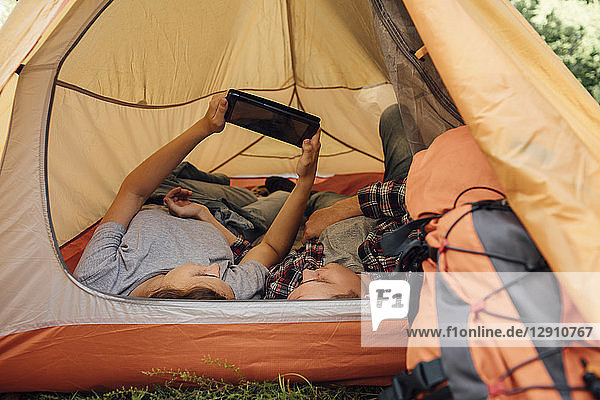 Young couple relaxing in tent  using digital tablet