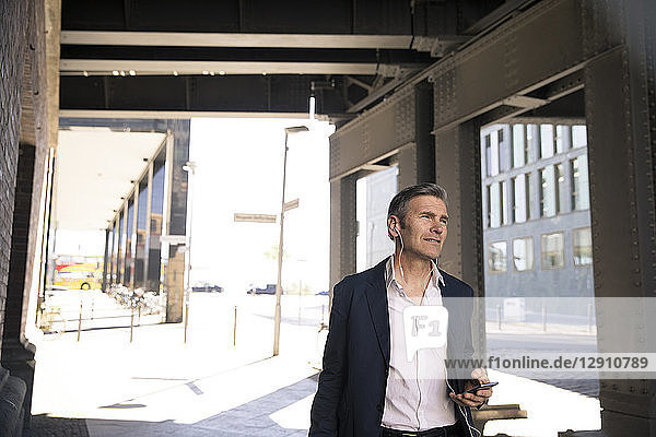 Mature businessman with earphones and smartphone on the go
