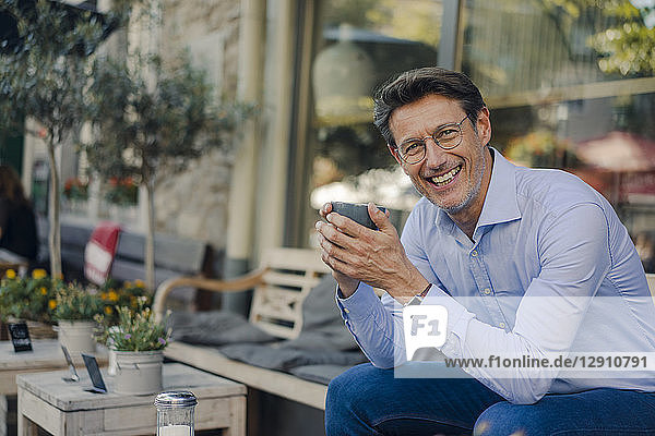 Mature businessman sitting in coffee shop  drinking coffee
