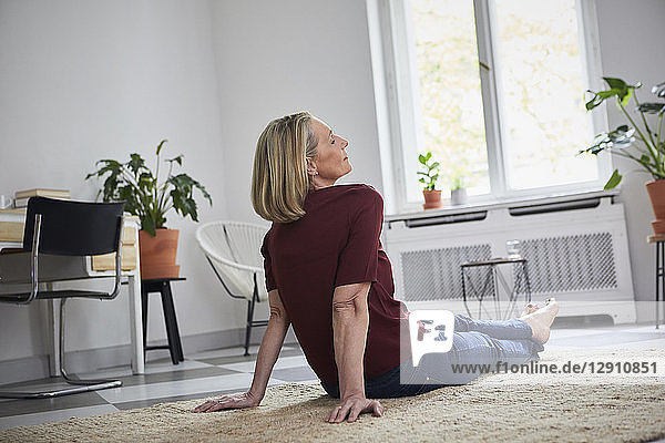 Relaxed mature woman sitting on the floor at home
