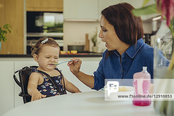 Mother helping disgusted baby daughter eating fruit pulp in kitchen