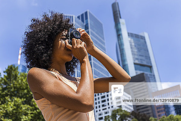 Germany  Frankfurt  young woman with curly hair taking photos in the city