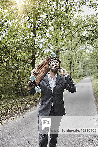Happy businessman with skateboard talking on smartphone on rural road