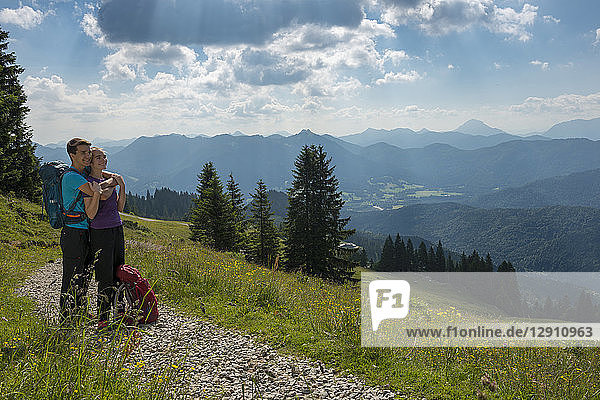 Germany  Bavaria  Brauneck near Lenggries  happy young couple having a break looking at view in alpine landscape