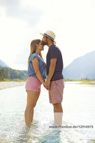 Young couple standing in water  kissing