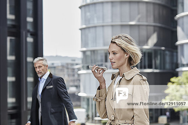 Germany  Duesseldorf  portrait of blond businesswoman wearing beige trenchcoat talking on mobile phone