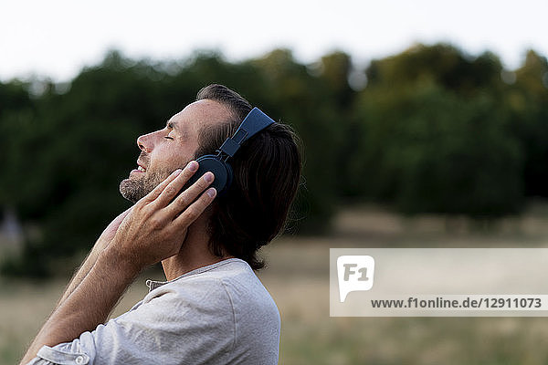 Smiling man listening to music with headphones in the nature