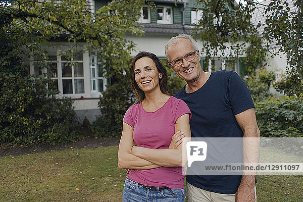Happy mature couple standing in garden of their home