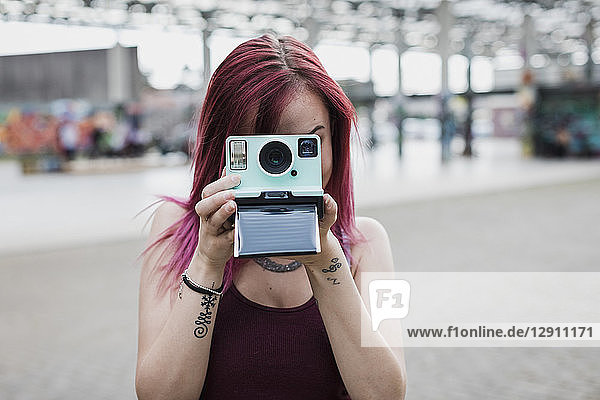 Young woman taking photo with instant camera outdoors