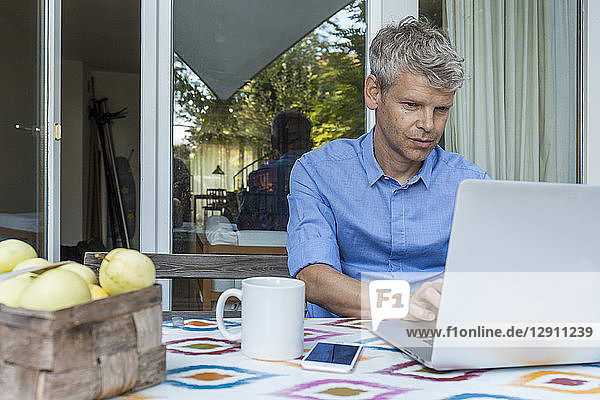 Portrait of mature man using laptop on terrace