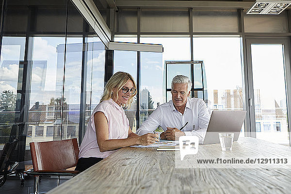 Businessman snd woman sitting in office  discussing project