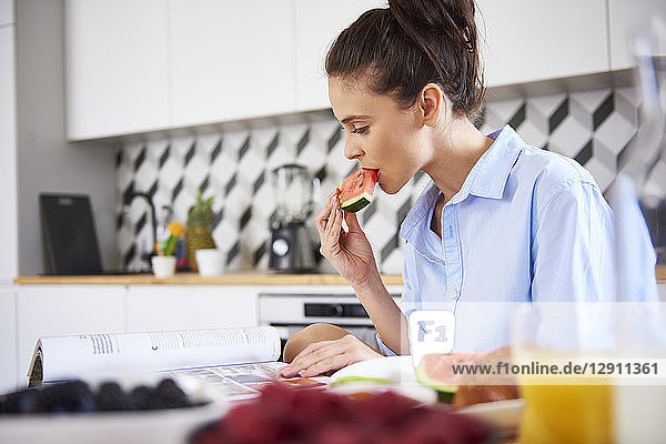 Young woman at home in kitchen  eating breakfast  reading book