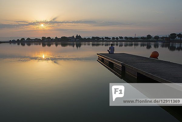Relaxed girl on the floating platform on the lake at sunrise
