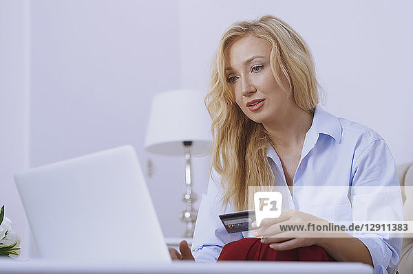 Blond woman sitting on couch  using laptop to make a payment with her credit card