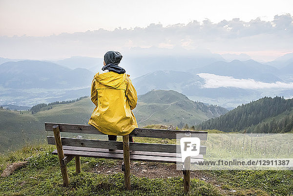 Austria  Tyrol  Fieberbrunn  Wildseeloder  woman sitting on bench with view on mountainscape