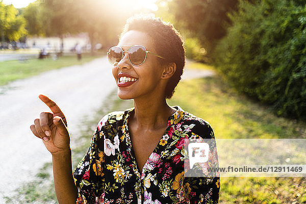 Happy young woman wearing sunglasses outdoors at sunset