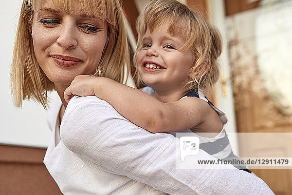 Smiling mother carrying her daughter piggyback in front of their house