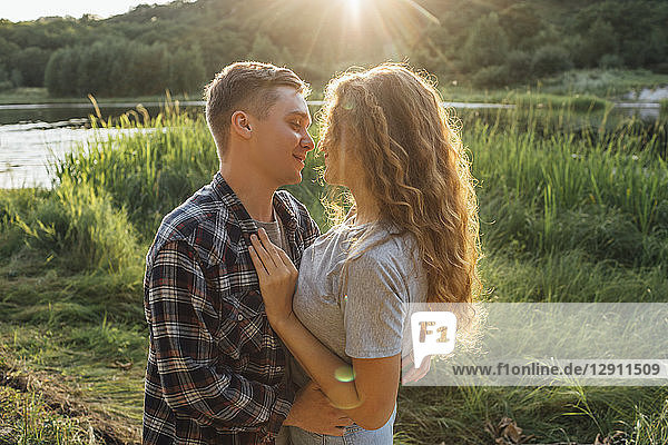Romantic couple spending time in nature  kissing at sunset
