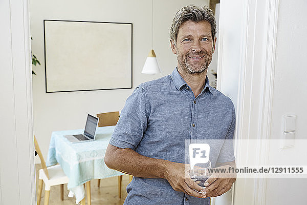 Mature man leaning against door case holding glass of water
