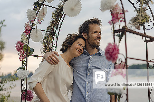 Happy couple embracing under wedding arch