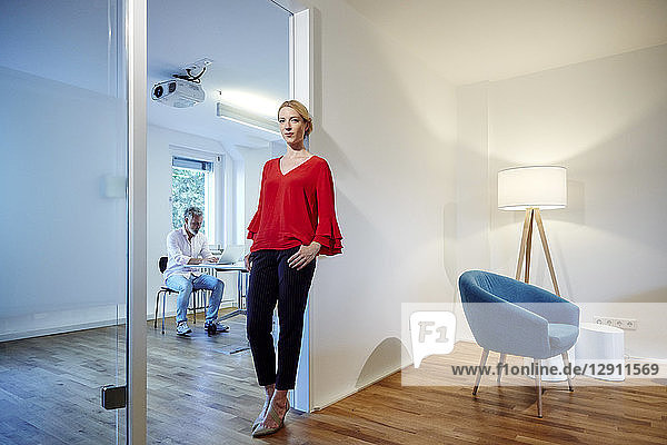 Portrait of young woman leaning against doorframe in office with colleague in background