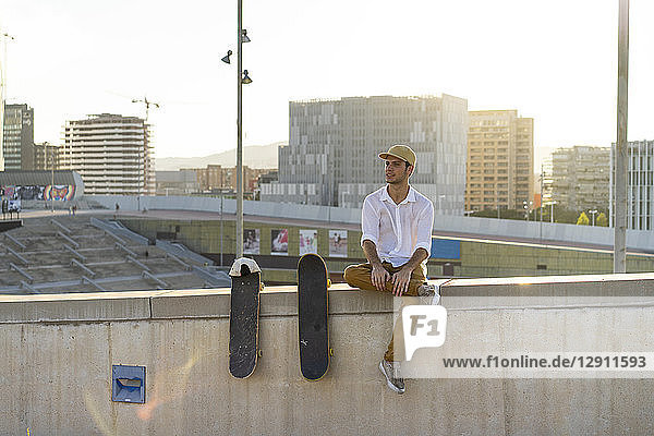 Young man sitting on urban wall next to skateboards at sunset