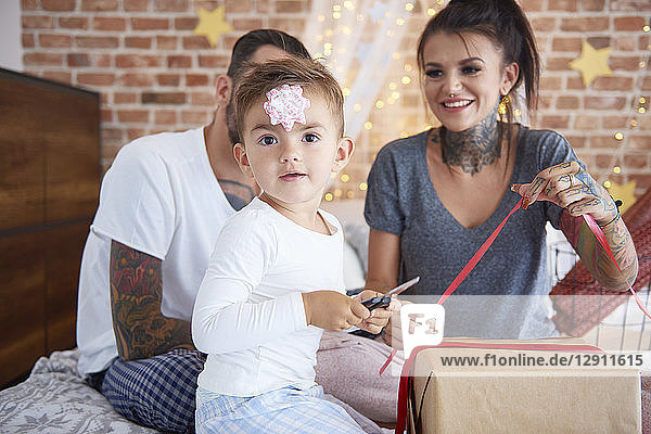 Portrait of boy opening Christmas present with his parents in bed