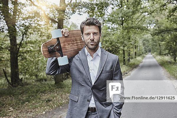 Portrait of businessman carrying skateboard on rural road