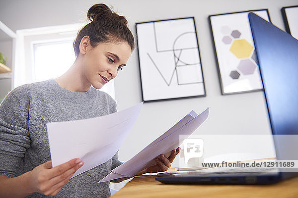 Young woman working from home  using laptop  reading papers