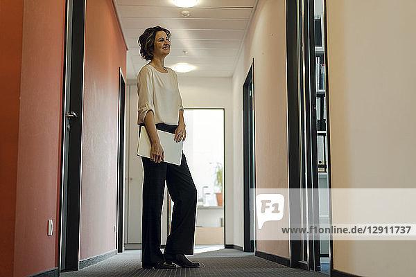 Businesswoman standing in office corridor  holding laptop