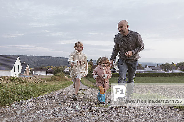 Father with two children running on field path