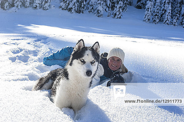 Austria  Altenmarkt-Zauchensee  portrait of smiling young woman lying with dog in snow