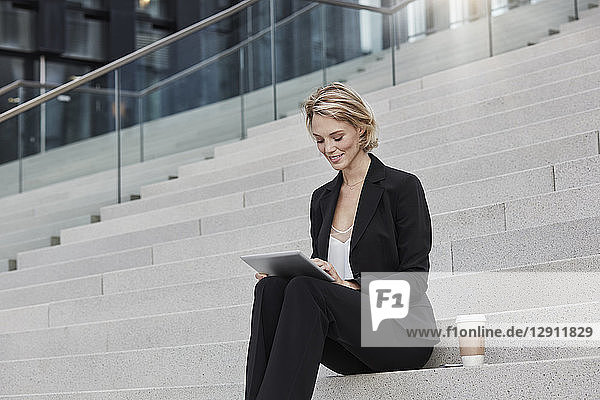 Blond businesswoman with coffee to goe sitting on stairs using tablet