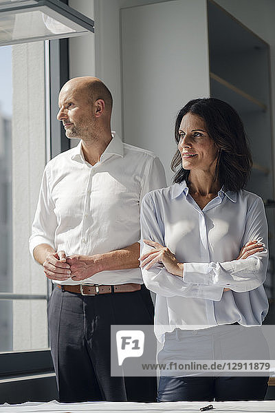 Two architects standing in office  looking out of window