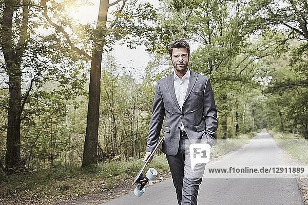 Businessman walking with skateboard on rural road