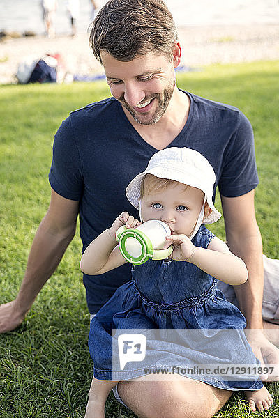 Father smiling at little daughter with baby bottle outdoors