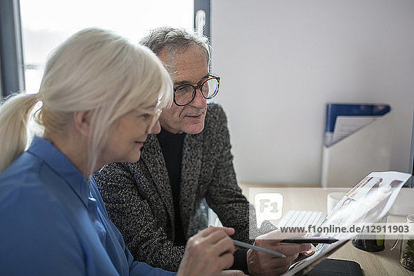 Two senior colleagues working together at desk in office examining photos