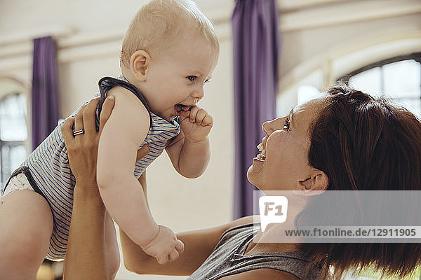 Sporty woman lifting up happy baby in training room