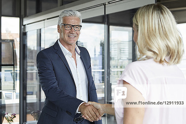 Businessman and woman shaking hands in office