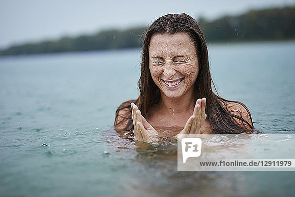 Portrait of freckled young woman bathing in lake on rainy day