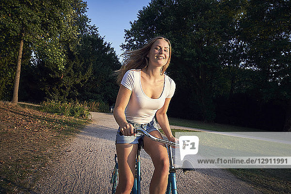 Cheerful young woman  riding bicycle in park